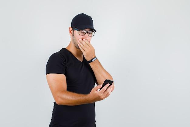 Młody człowiek w czarnej koszulce, czapce, okularach, patrząc na smartfona z ręką na ustach i wyglądający na zaskoczonego