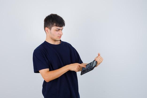 Młody człowiek w czarnej koszulce dokonywania obliczeń na kalkulatorze i patrząc zajęty, widok z przodu.