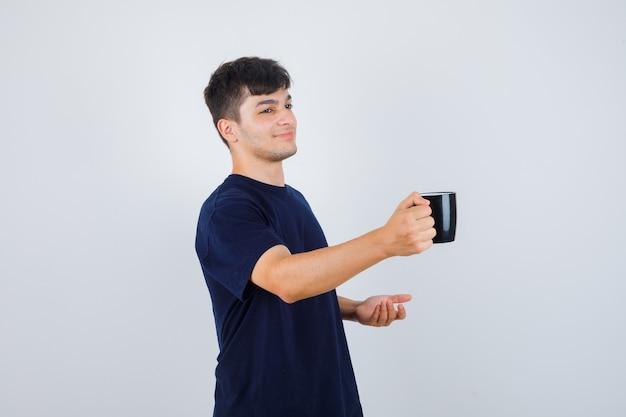 Młody człowiek w czarnej koszulce, oferując filiżankę herbaty i delikatnie patrząc z przodu.