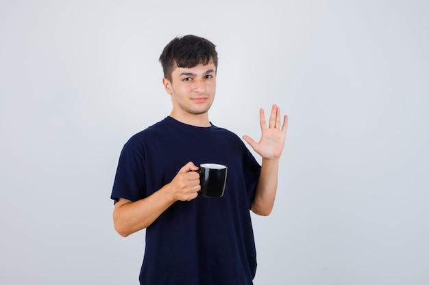 Młody człowiek w czarnej koszulce, trzymając filiżankę herbaty, pokazując dłoń i patrząc pewnie, z przodu.