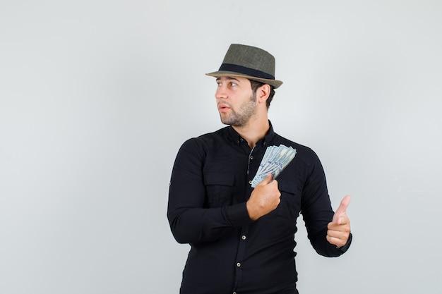 Młody człowiek w czarnej koszuli, kapelusz gospodarstwa pieniądze ze znakiem palca