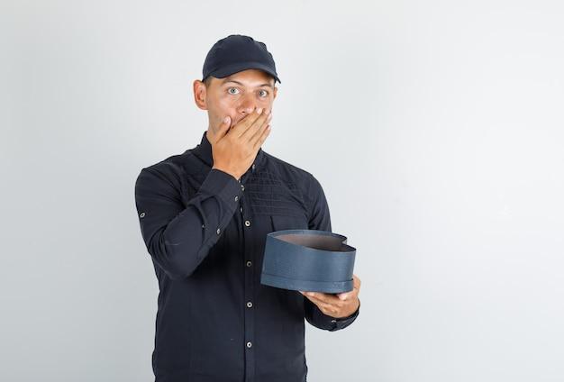 Młody człowiek w czarnej koszuli z czapką trzyma otwarte pudełko i wygląda na zaskoczonego