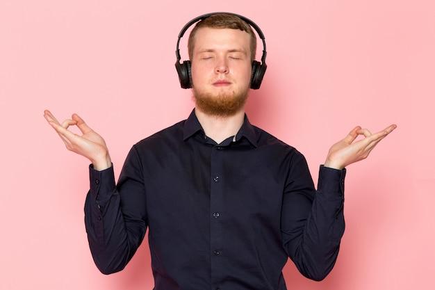 Młody człowiek w czarnej koszuli z czarnymi słuchawkami