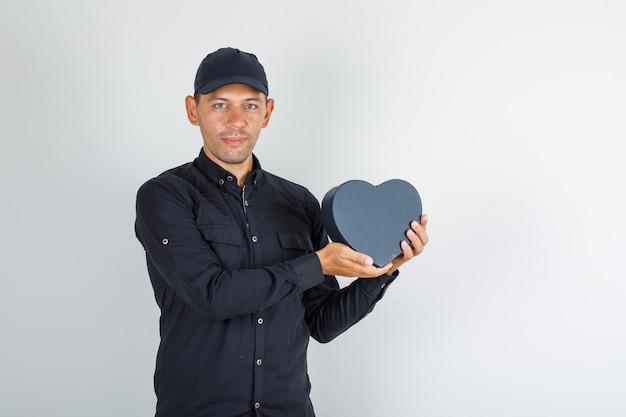 Młody człowiek w czarnej koszuli z kapelusza, trzymając pudełko