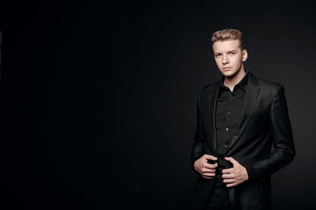 Młody człowiek w czarnej kurtce na czarnym tle