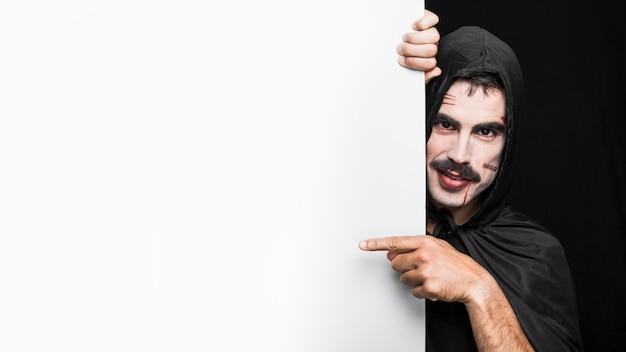 Młody człowiek w czarnej pelerynie z kapiszonem pozuje w studiu
