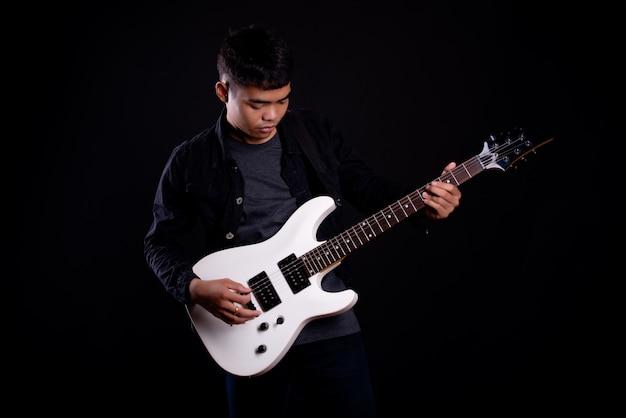 Młody człowiek w czarnej skórzanej kurtce z gitarą elektryczną