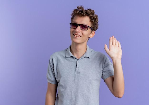 Młody człowiek w czarnych okularach na sobie szarą koszulkę polo patrząc na bok uśmiechnięty macha ręką gest pozdrowienia stojąc na niebieskiej ścianie