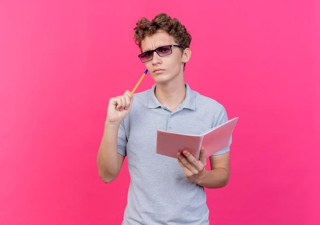 Młody człowiek w czarnych okularach na sobie szarą koszulkę polo trzymając notebook z piórem, patrząc z zamyślonym wyrazem myśli na różowo
