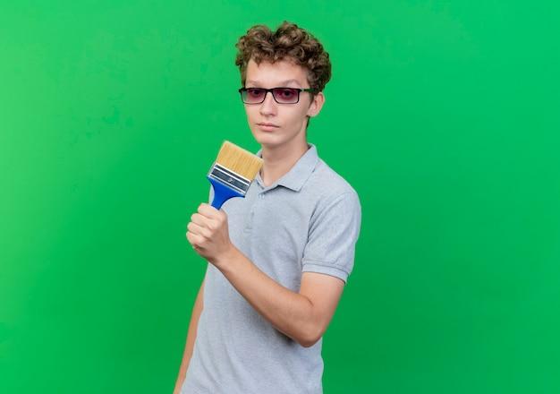 Młody człowiek w czarnych okularach na sobie szarą koszulkę polo, trzymając pędzel loking w aparacie z poważną twarzą sceptyka na zielono