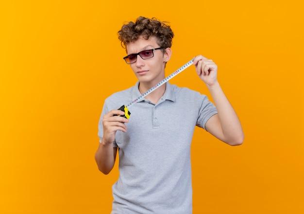 Młody człowiek w czarnych okularach na sobie szarą koszulkę polo trzymając środek taśmy uśmiechnięty szczęśliwy i pozytywny na pomarańczowo