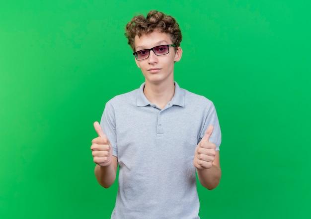 Młody człowiek w czarnych okularach na sobie szarą koszulkę polo uśmiechnięty szczęśliwy i pozytywny pokazując kciuki do góry stojąc nad zieloną ścianą
