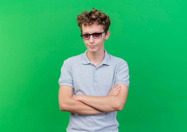 Młody człowiek w czarnych okularach na sobie szarą koszulkę polo z poważną twarzą sceptyka ze skrzyżowanymi rękami na zielono