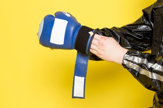 Młody człowiek w czarnym garniturze sportowym i niebieskie rękawice bokserskie