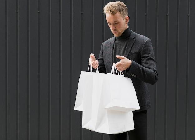 Młody człowiek w czerni patrzeje w torba na zakupy