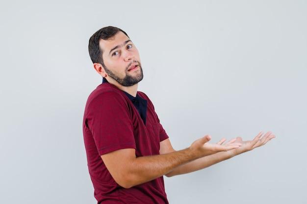 Młody człowiek w czerwonej koszulce pokazuje bezradny gest i wygląda na zmartwionego, widok z przodu.