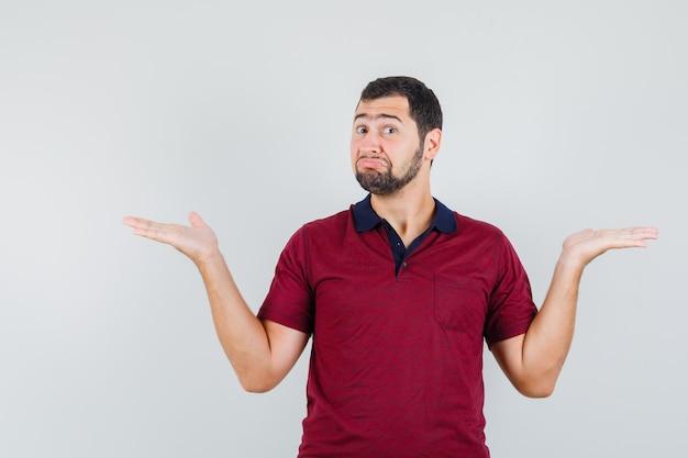 Młody człowiek w czerwonej koszulce pokazuje bezradny gest i wygląda nieszczęśliwy, widok z przodu.