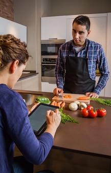 Młody człowiek w domowej kuchni przygotowuje jedzenie i kobieta szuka przepis w elektronicznym tablecie. koncepcja nowoczesnego stylu życia rodziny.