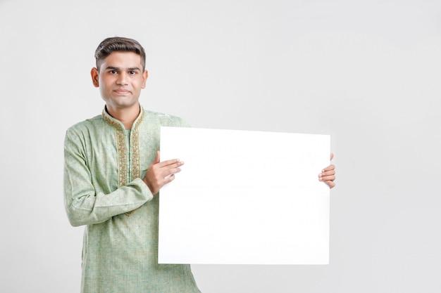 Młody człowiek w etnicznej odzieży i pokazywać puste miejsce znaka deskę