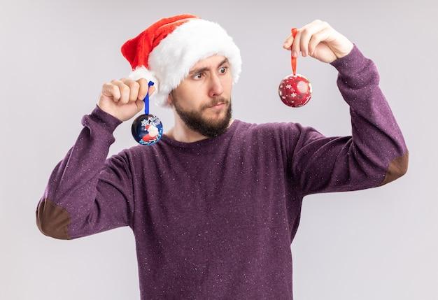 Młody człowiek w fioletowym swetrze i czapce mikołaja w śmiesznych okularach trzymający bombki patrząc na nich zdezorientowany, próbując dokonać wyboru stojąc nad białą ścianą