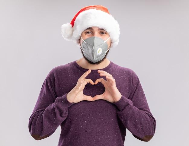 Młody człowiek w fioletowym swetrze i kapeluszu santa na sobie maskę ochronną na twarz patrząc na aparat robiąc gest serca palcami stojącymi na białym tle