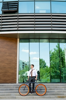 Młody człowiek w formalnej odzieży patrząc na bok stojąc na schodach z zewnątrz współczesnego centrum biznesowego