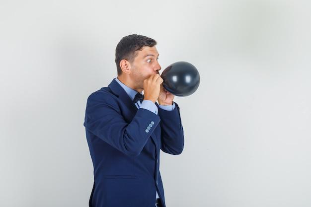 Młody człowiek w garniturze dmuchanie czarny balon