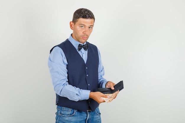 Młody człowiek w garniturze, dżinsach, trzymając pieniądze i portfel i patrząc poważnie