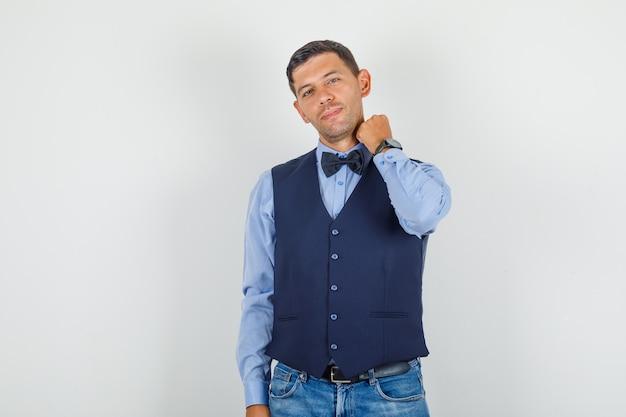 Młody człowiek w garniturze, dżinsy pozowanie, trzymając za kołnierz i wyglądając stylowo