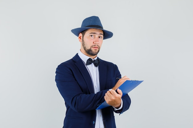 Młody człowiek w garniturze, kapelusz, robienie notatek w schowku i rozsądny wygląd, widok z przodu.