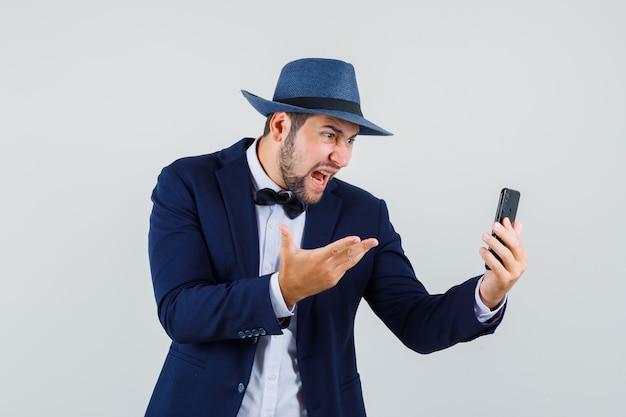 Młody człowiek w garniturze, krzycząc podczas rozmowy wideo i patrząc zły, widok z przodu kapelusz.