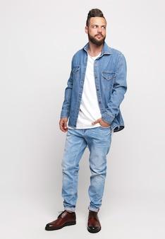 Młody człowiek w garniturze. przystojny mężczyzna w dżinsowej kurtce i dżinsach