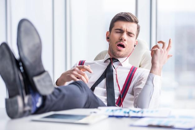 Młody człowiek w garniturze słucha muzyki w słuchawkach w biurze.