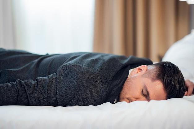 Młody człowiek w garniturze śpi na łóżku