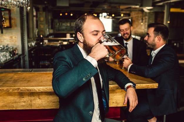 Młody człowiek w garniturze stać w barze i pić piwo. za nim stoi dwóch innych mężczyzn. oni rozmawiają.