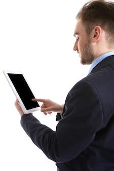 Młody człowiek w garniturze za pomocą tabletu, na białym tle