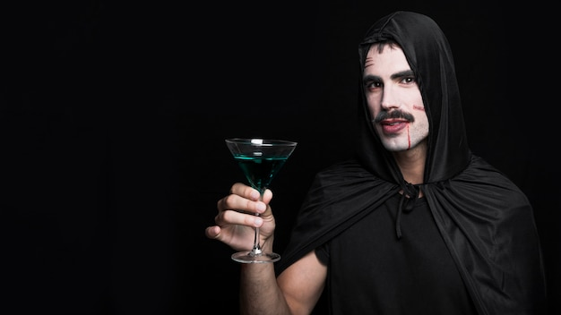 Młody człowiek w halloweenowym kostiumu pozuje w studiu i trzyma szkło