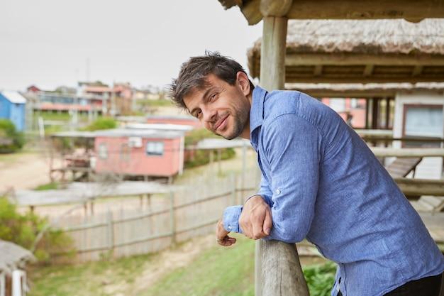 Młody człowiek w jasnoniebieskiej koszuli, opierając się na drewnianej poręczy tarasu swojej kabiny, patrząc w kamerę i uśmiechając się.