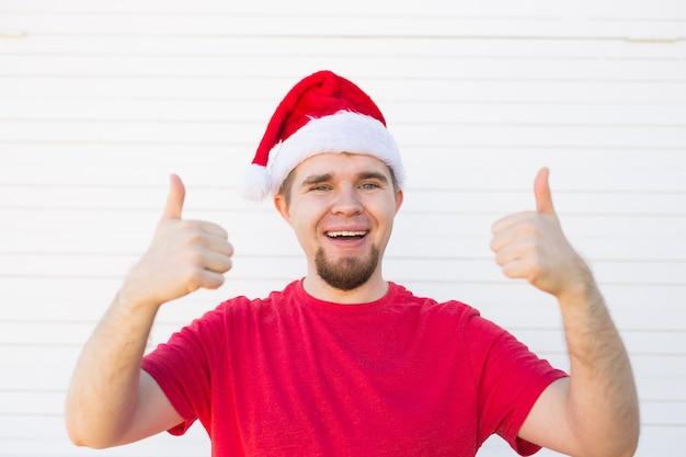 Młody człowiek w kapeluszu boże narodzenie, robiąc kciuk znak na białym tle