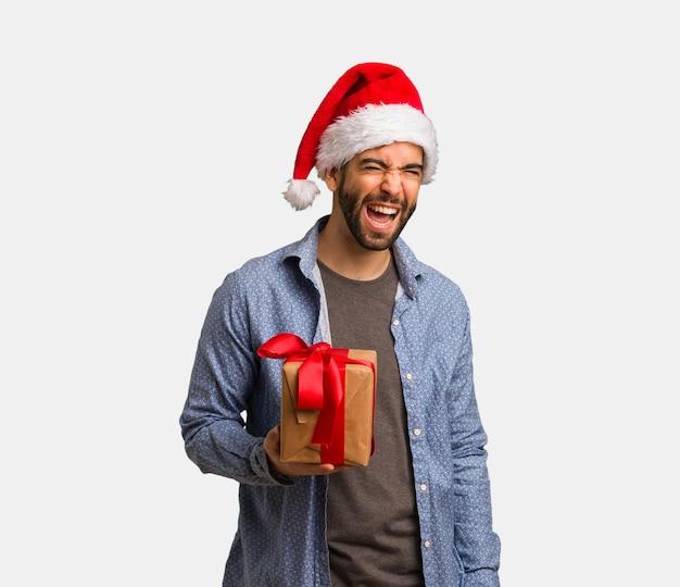 Młody człowiek w kapeluszu santa mrugając, zabawny, przyjazny i beztroski gest