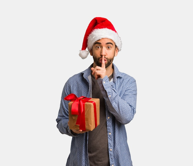 Młody człowiek w kapeluszu santa zachowując sekret lub prosząc o ciszę