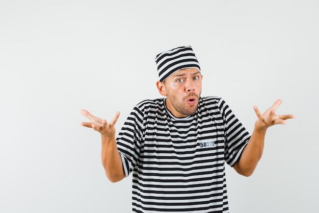 Młody człowiek w kapeluszu t-shirt w paski, trzymając ręce w pytającym geście i patrząc zdziwiony