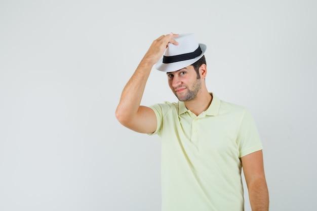 Młody człowiek w kapeluszu w t-shirt i wyglądający przystojny.