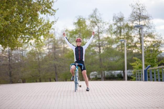 Młody człowiek w kasku i odzież sportowa podnosząc ręce i świętuje zwycięstwo podczas jazdy na rowerze na chodniku w parku