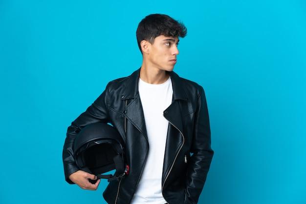 Młody człowiek w kasku motocyklowym na białym tle niebieski patrząc z boku