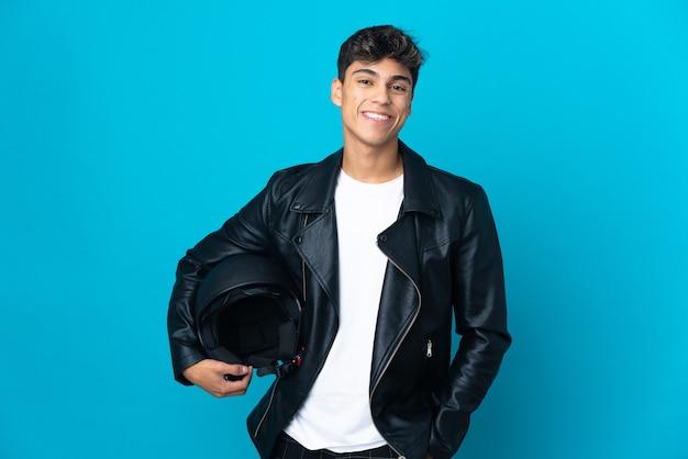 Młody człowiek w kasku motocyklowym na białym tle niebieski pozowanie z rękami na biodrze i uśmiechnięty
