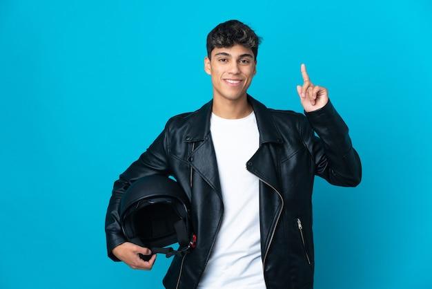 Młody człowiek w kasku motocyklowym na białym tle niebieski wskazując na świetny pomysł