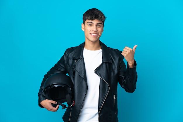 Młody człowiek w kasku motocyklowym na na białym tle niebieski, wskazując na bok, aby przedstawić produkt