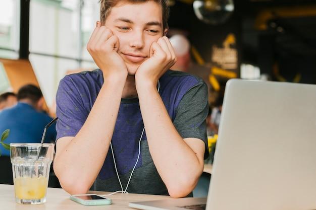 Młody człowiek w kawiarni robi wideo wezwaniu