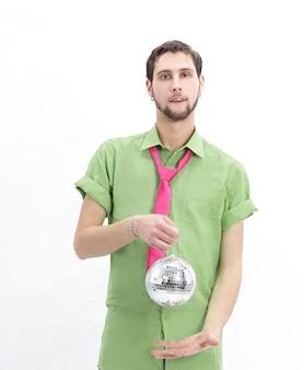 Młody człowiek w kolorowe ubrania z kulą lustrzaną. na białym tle na białej ścianie